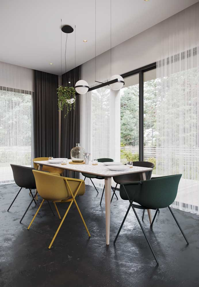 Nessa sala de jantar, o voil foi usado no forro, sobre ela, um tecido preto e encorpado que garante um efeito blecaute