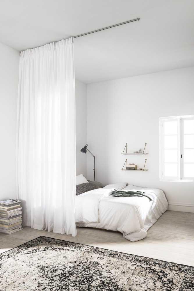 Nesse outro quarto, a cortina de voil serve para delimitar os espaços do ambiente