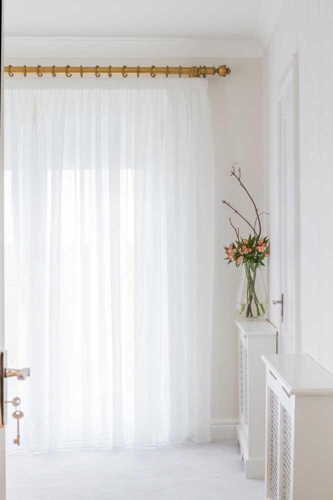 Nesse ambiente todo clean, a cortina de voil branco ganha destaque graças ao trilho dourado que a sustenta