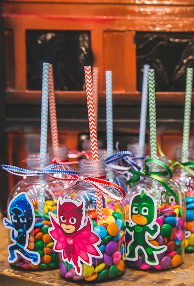 Use materiais reciclados para fazer a decoração PJ Masks. Pegue garrafas plásticas e personalize com os personagens.