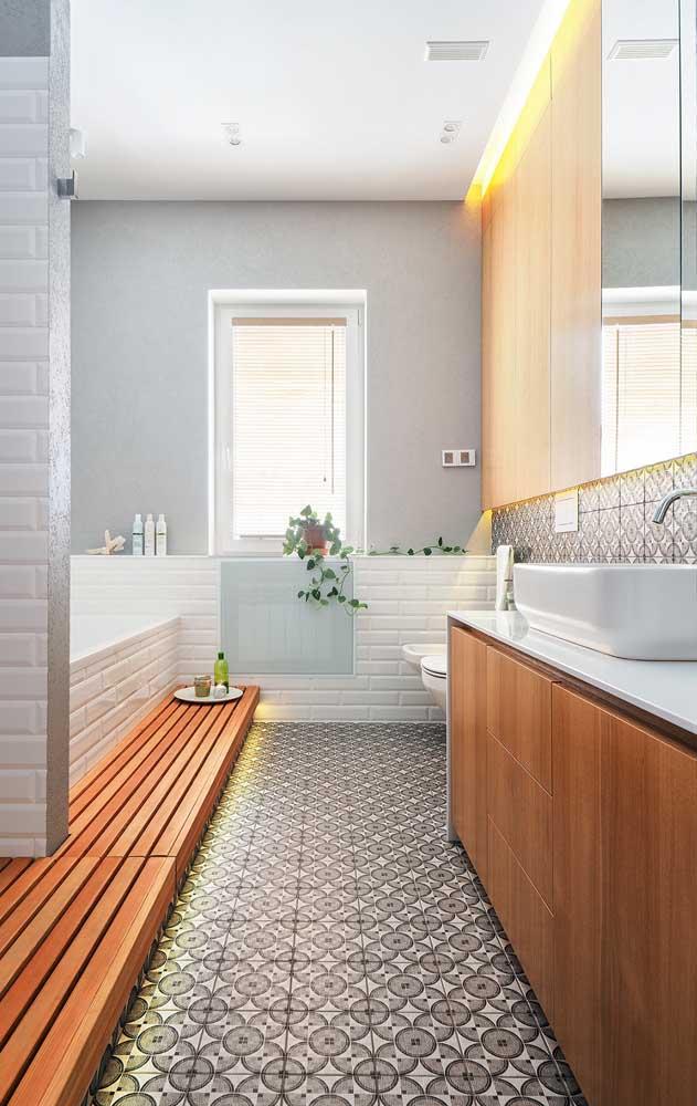 Banheiro com revestimentos brancos, móveis de madeira e um leve toque acinzentado no chão
