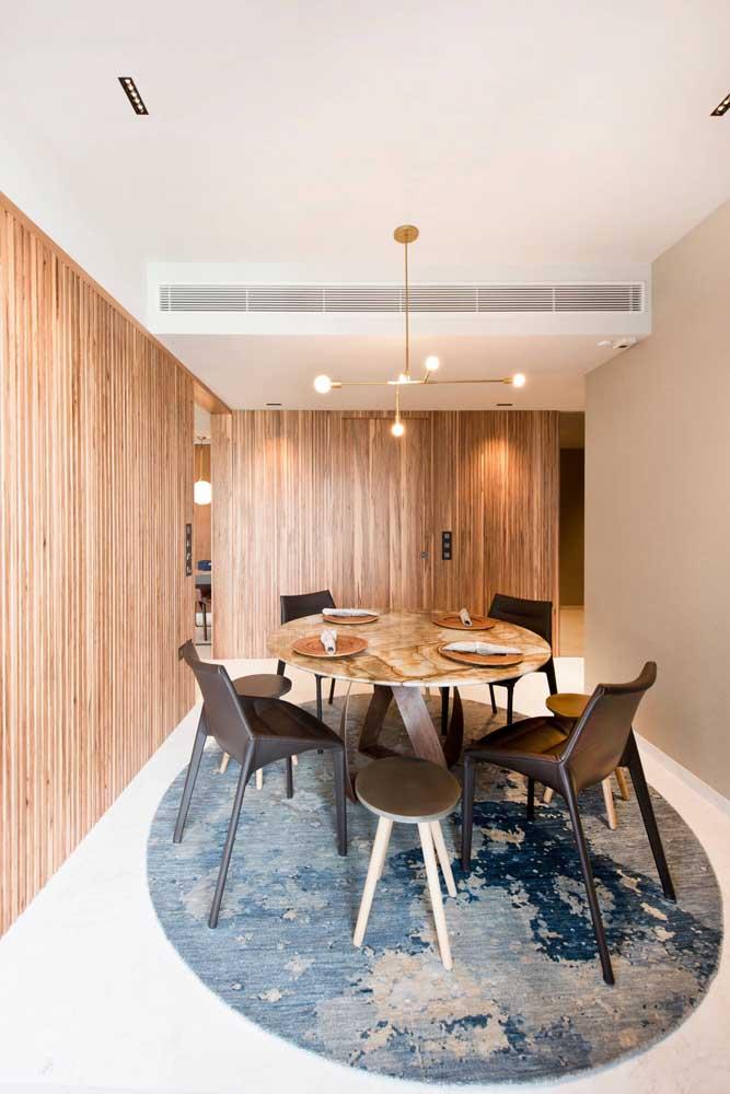 Um painel de madeira rústica reveste as paredes dessa sala de jantar, enquanto isso, o branco na parede e no teto refresca os olhos