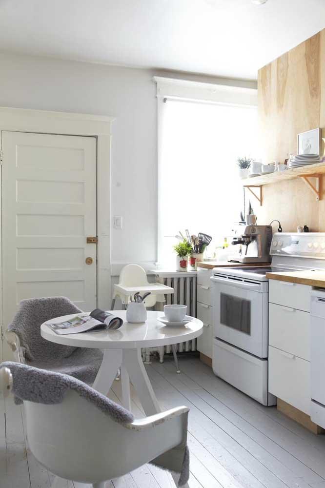 Essa pequena cozinha branca trouxe a madeira em detalhes no armário e na bancada da pia