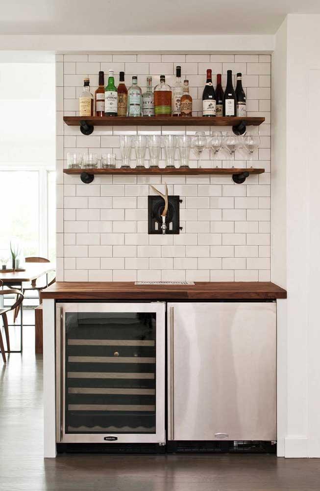 Para destacar o barzinho no ambiente, a solução foi apostar em um tom escuro de madeira para as prateleiras e o pequeno balcão