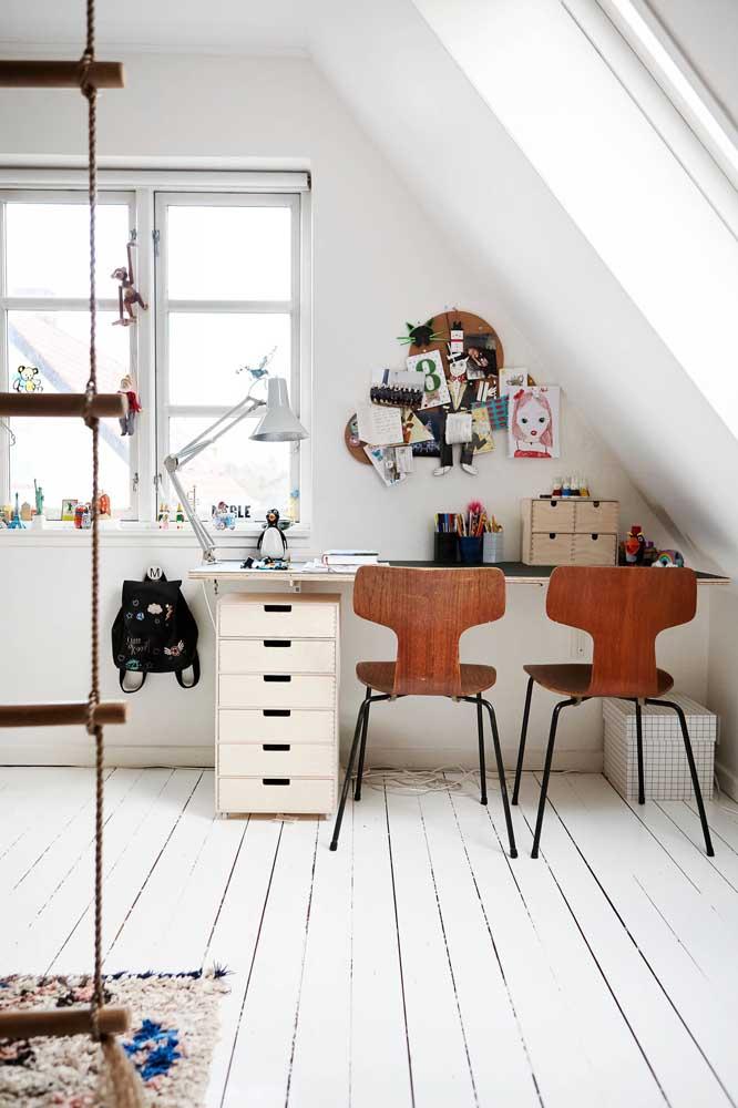 Nesse quarto de base branca, as cadeiras de madeira se destacam