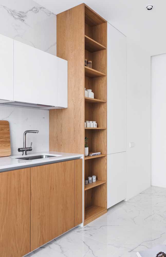 Móveis de cozinha brancos e em madeira; no piso e nas paredes foi usado um porcelanato com efeito mármore na cor branca