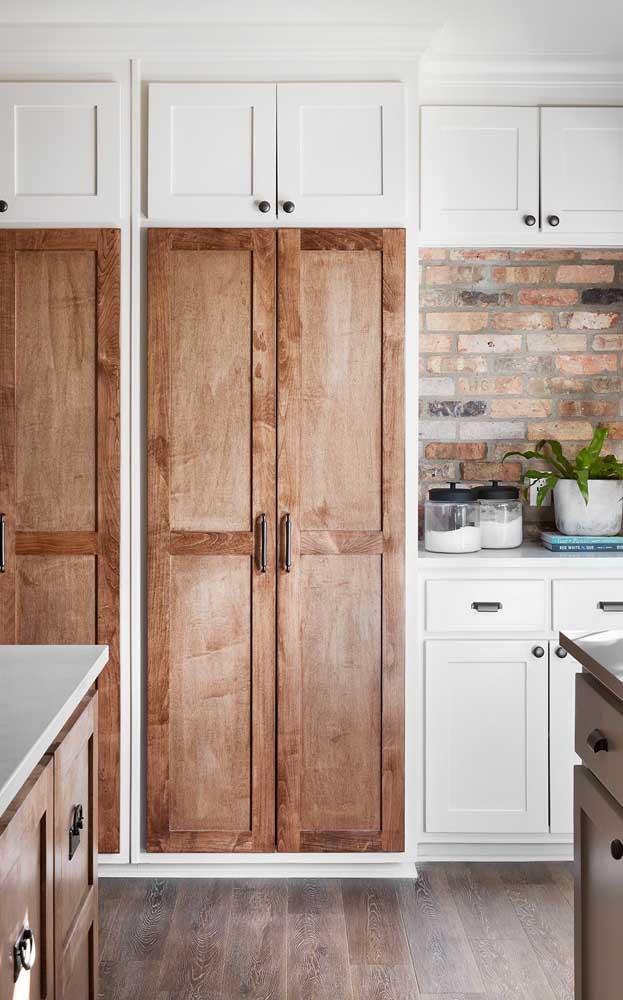 A madeira rústica casou perfeitamente com os tijolinhos de demolição na parede; o branco, por sua vez, marca presença no armário de marcenaria clássica fazendo um belo contraponto com a madeira
