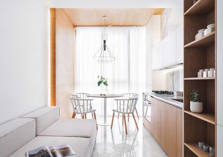 Sala de estar e jantar integradas e igualmente decoradas em tons de branco e madeira