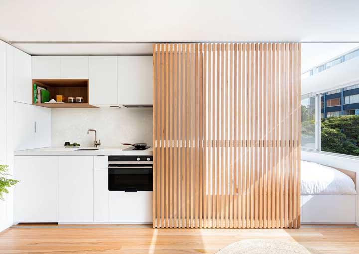 Aqui, o painel de madeira se destaca pela beleza, funcionalidade e contraste com o branco