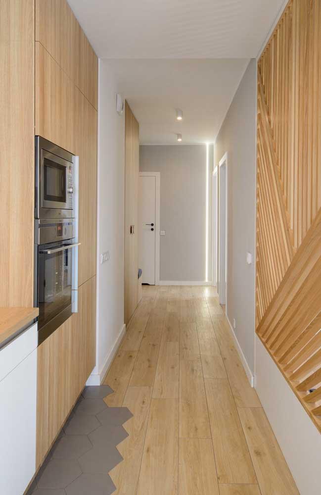 Aqui, a madeira entra na composição por meio de um lindo painel no corredor; o material se repete também nos armários
