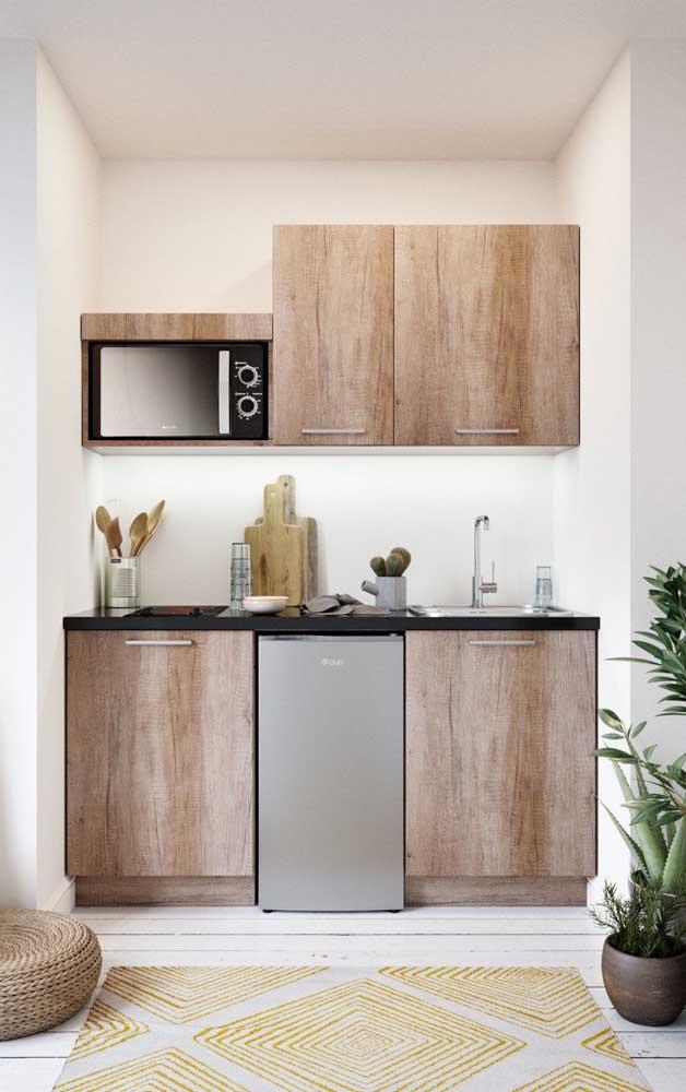 Uma cozinha pequena decorada em tons de branco e madeira, só que uma madeira mais escura, sugerindo um estilo mais rústico para a decor