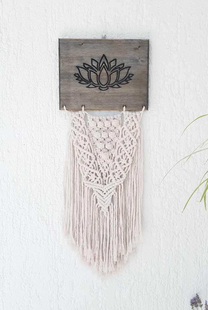 Essa decoração boho chic apostou no uso da Flor de Lótus talhada na madeira que sustenta a arte em macramê