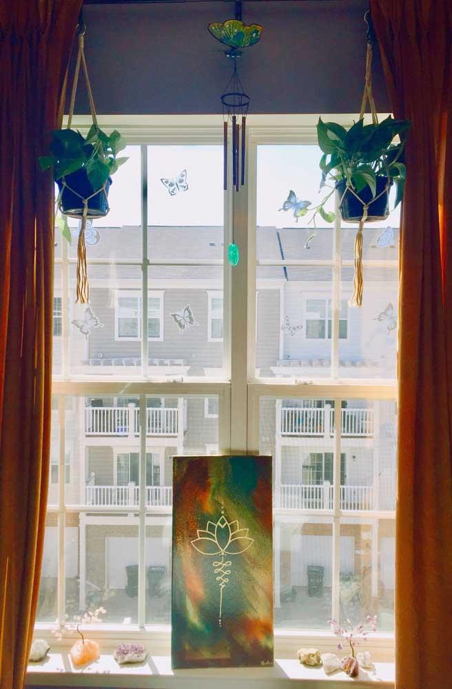 Na parte superior da janela, a Flor de Lótus aparece como base do sino dos ventos, mais abaixo, ela ressurge estampada no quadro