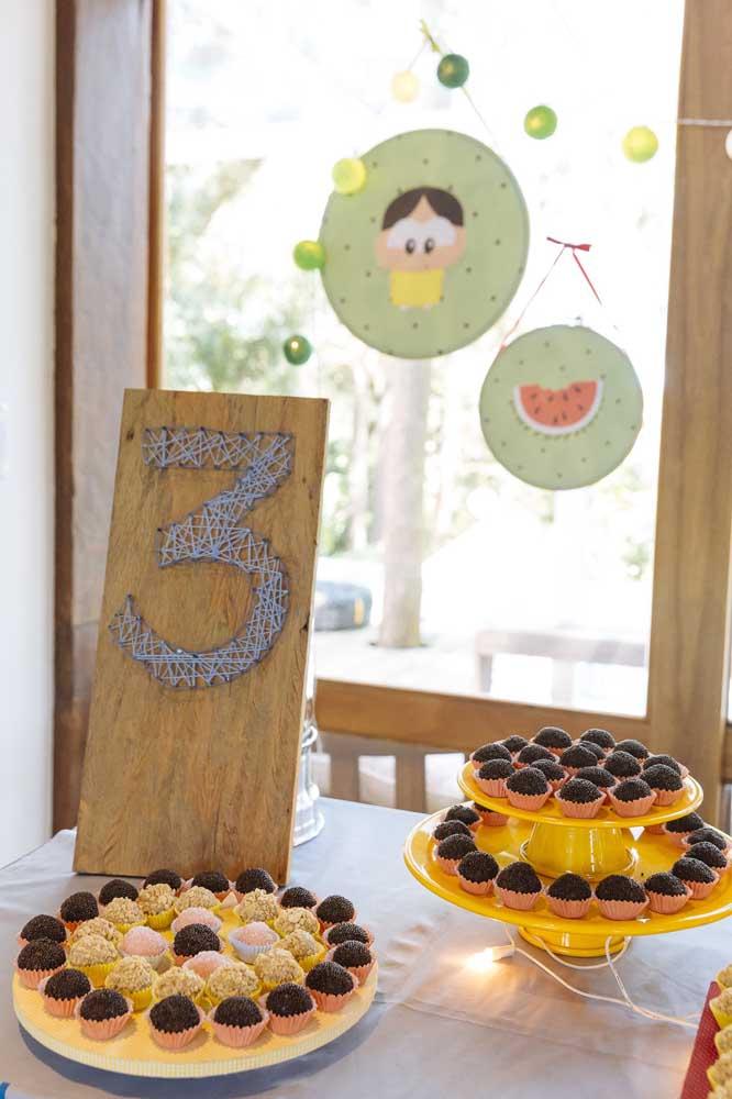 Parte da mesa de doces da festa Magali com paleta de cores em verde e amarelo