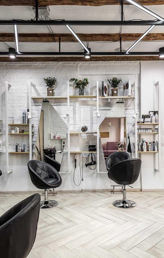 A iluminação de estilo industrial e os espelhos com recortes modernos casaram perfeitamente nesse projeto de salão de beleza