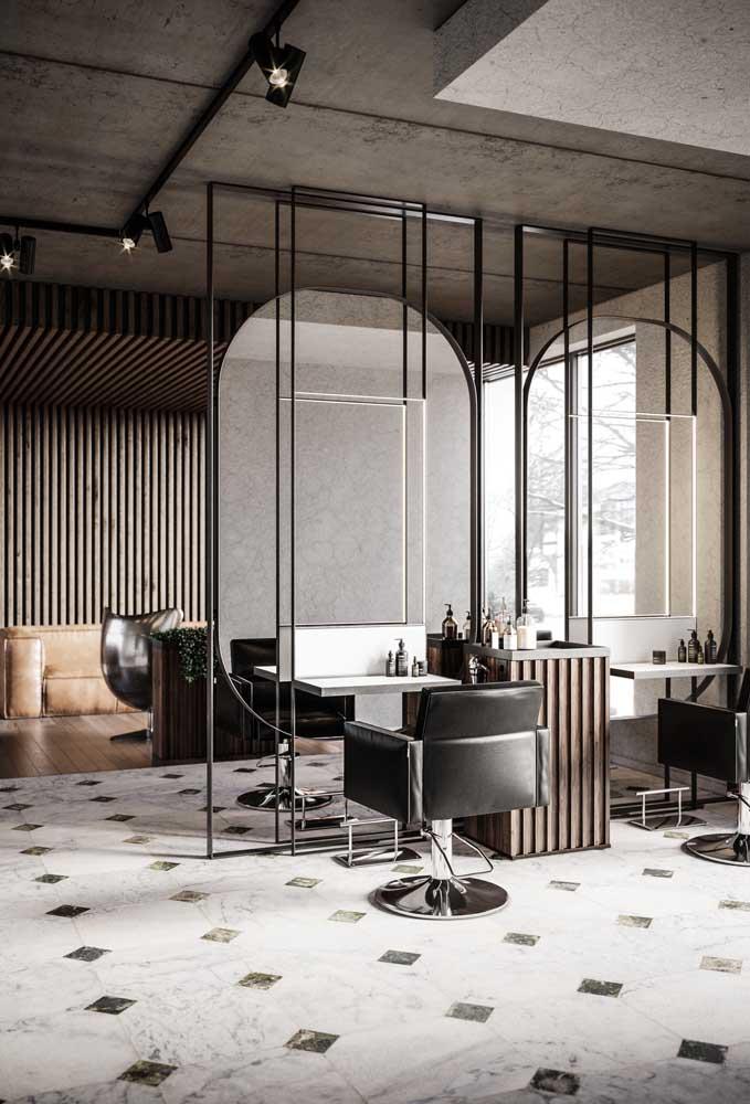 Salão com estilo industrial e moderno; repare que os espelhos ajudam a criar uma divisória no ambiente