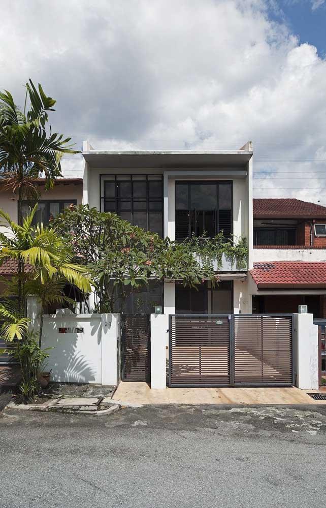 Modelo de casa de alvenaria com dois pavimentos, portão para garagem e portão para entrada social