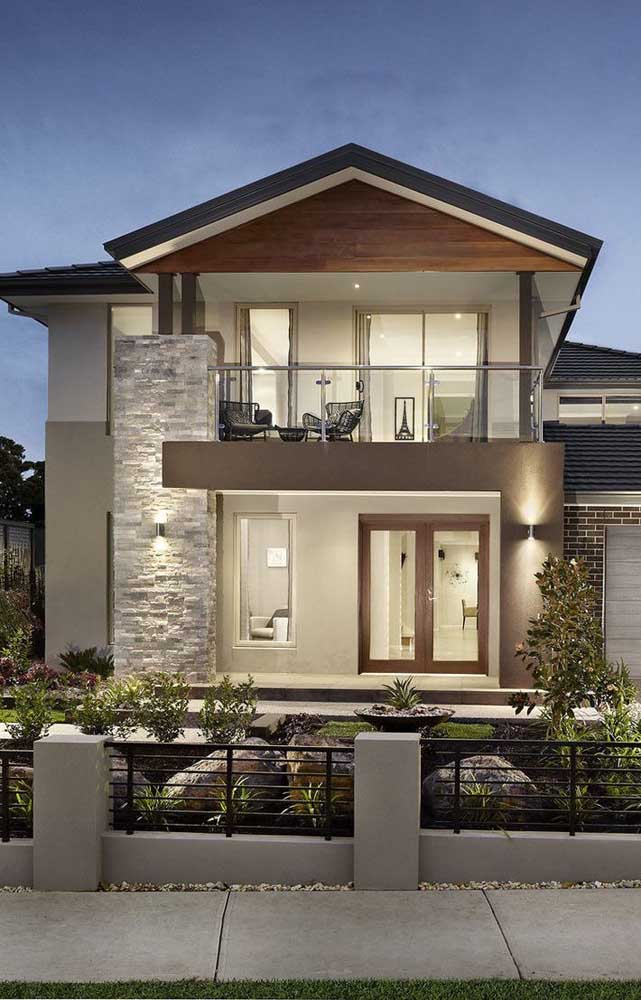 Casa elegante feita em alvenaria com detalhes em pedras e grandes janelas viradas para a fachada