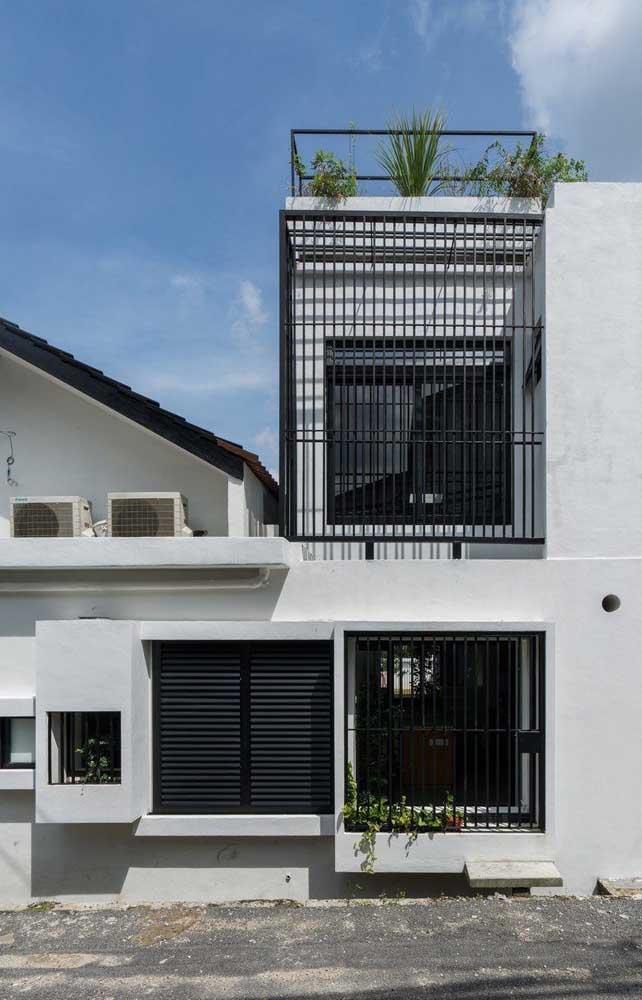 Fachada de casa de alvenaria simples; destaque para as grades que reforçam a segurança do imóvel
