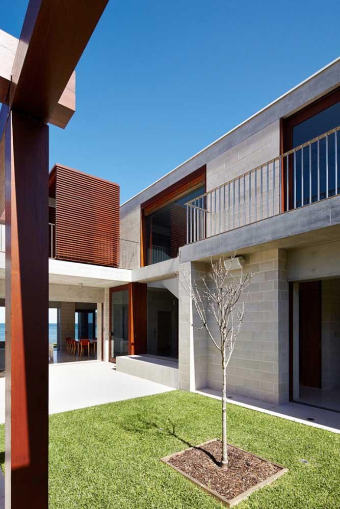 Casa de alvenaria com jardim central; os blocos de concreto à vista se destacam nessa construção