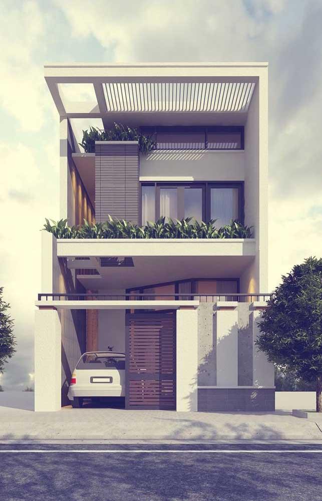 Casa de alvenaria moderna com dois pavimentos e varanda, além da garagem interna