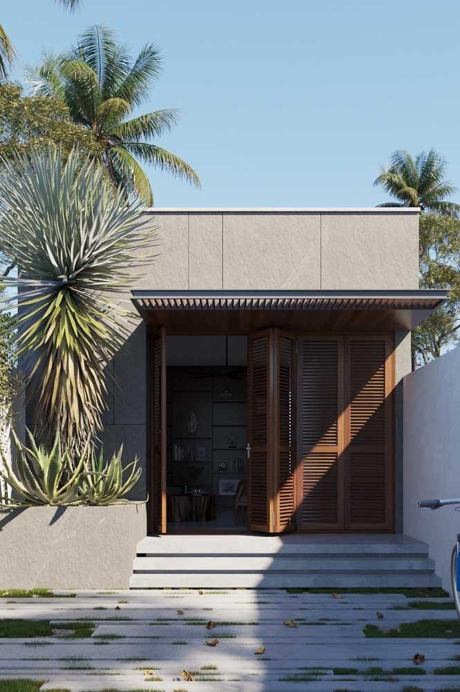 Fachada de uma casa pequena de alvenaria com acabamento em concreto natural