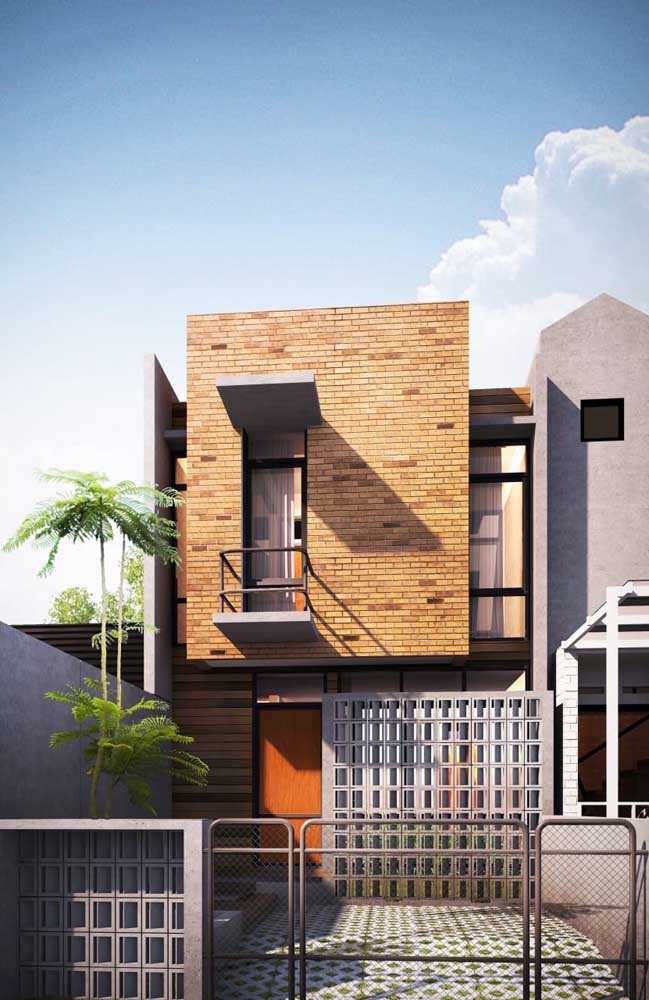 O combinação entre tijolinhos, madeira e concreto ficou perfeita na fachada da casa de alvenaria