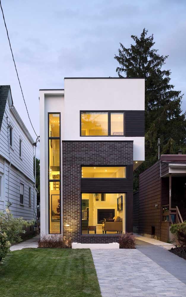 Mais um modelo de casa de alvenaria pequena para você se inspirar, essa aqui conta com acabamento em tijolo à vista na fachada e jardim gramado ao canto do terreno