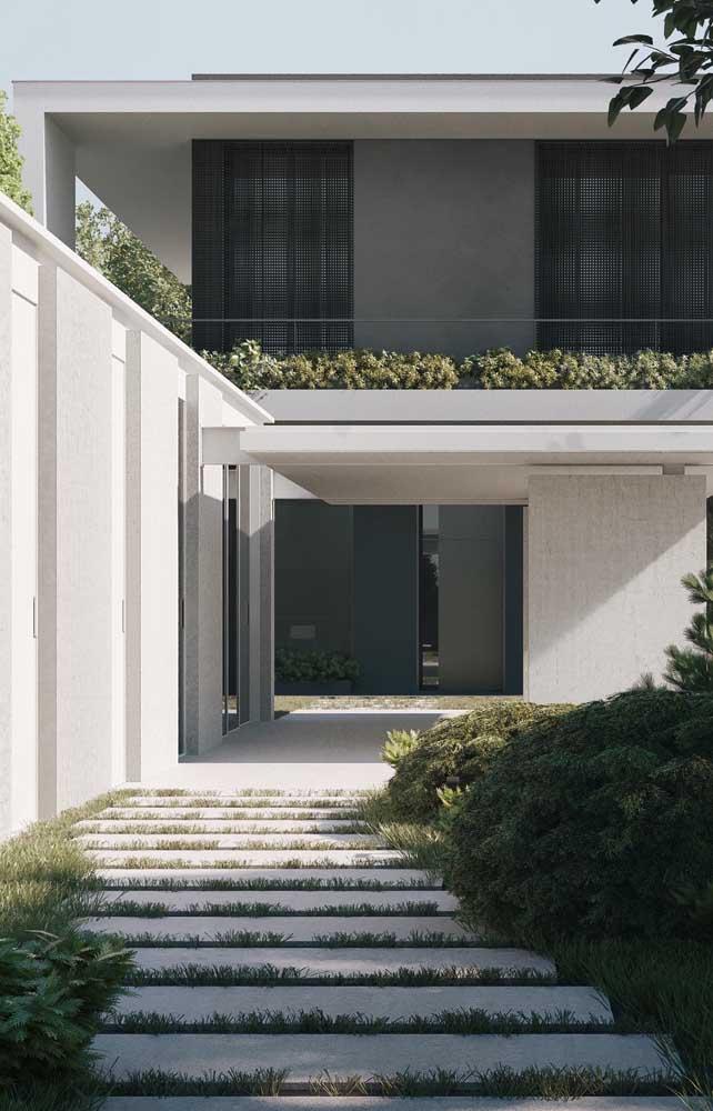 Vista da entrada da casa de alvenaria em estilo contemporâneo com dois pavimentos e jardim exclusivo