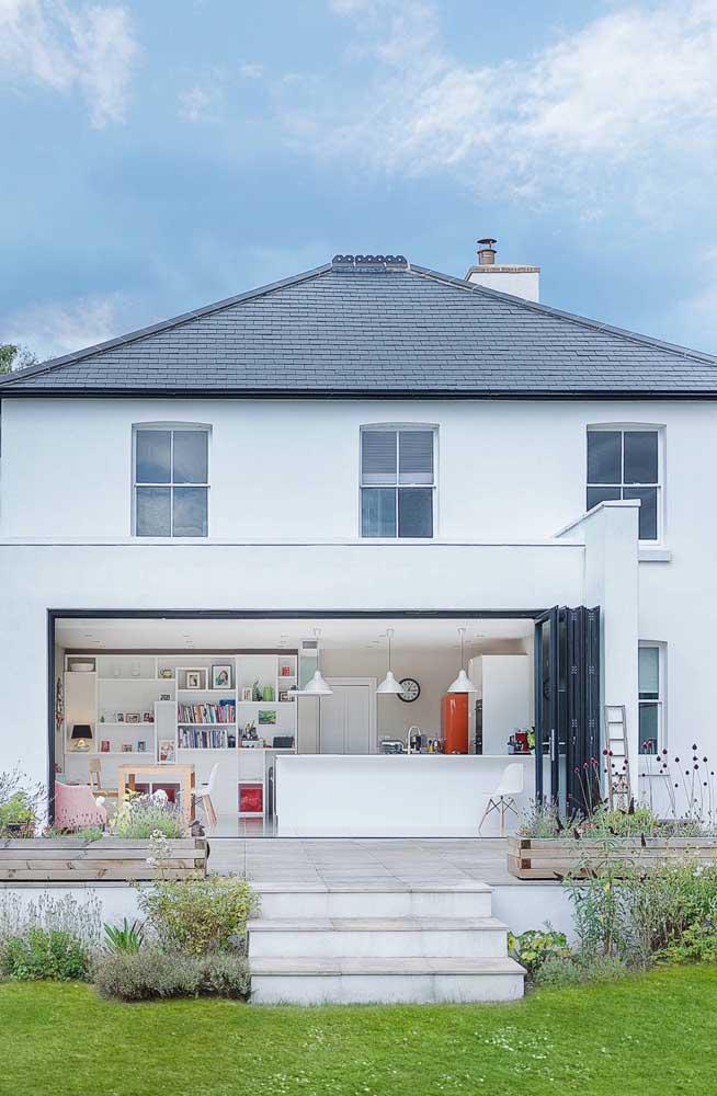 Inspiração de casa de alvenaria com porta sanfonada de vidro possibilitando o acesso entre o jardim e os cômodos integrados