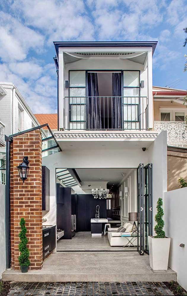 Casa de alvenaria pequena com dois pavimentos e terraço aberto com acabamento em cerâmica de tijolos coloridos