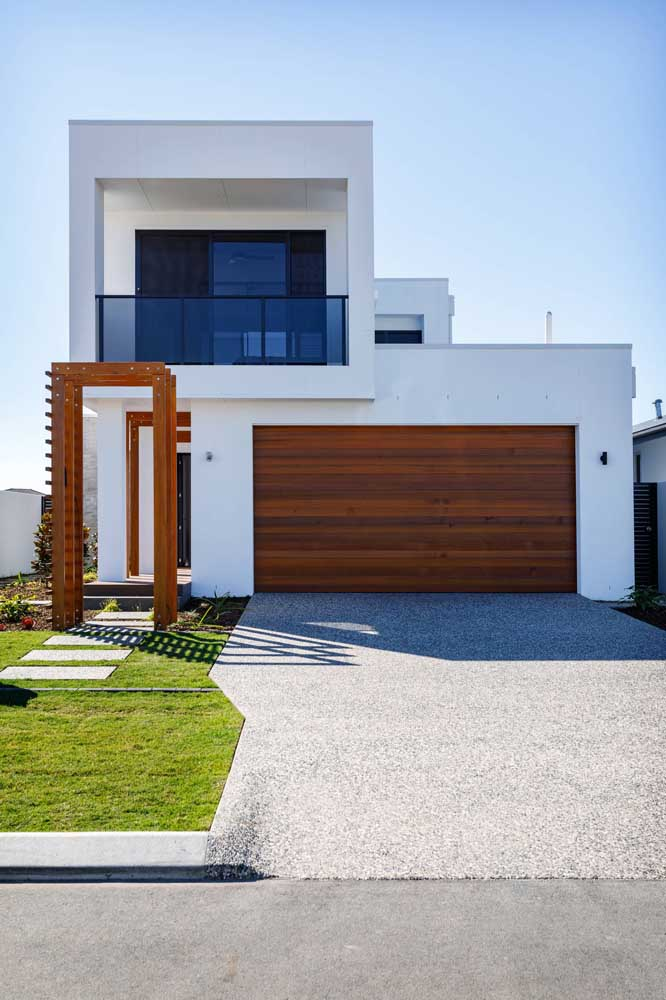 Fachada de uma casa de alvenaria moderna e minimalista com portão de madeira para a garagem interna