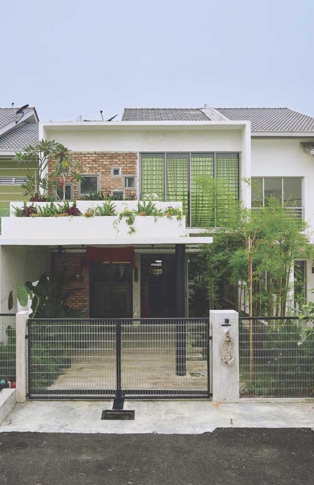 Modelo de casa de alvenaria onde foi incluso o uso de tijolos à vista, varanda, garagem coberta e jardim no beiral da fachada