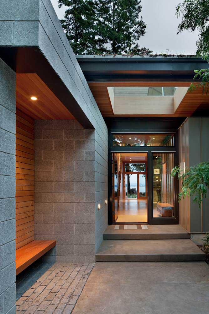 Vista da entrada da casa de alvenaria com acabamento em blocos de concreto aparente