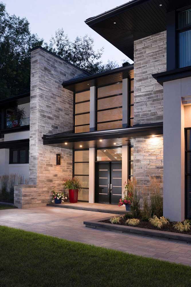 A entrada dessa casa ganhou um toque de elegância e aconchego com o uso dos tijolinhos à vista e o projeto de iluminação