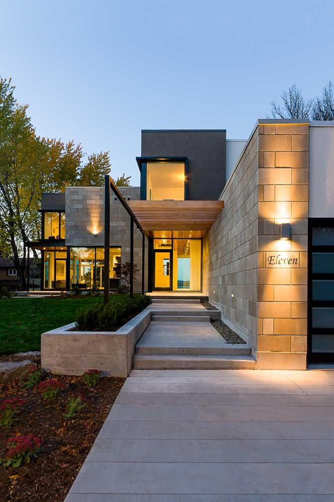 Casa de alvenaria com corredor de blocos de concreto aparente; destaque para a iluminação especial na fachada
