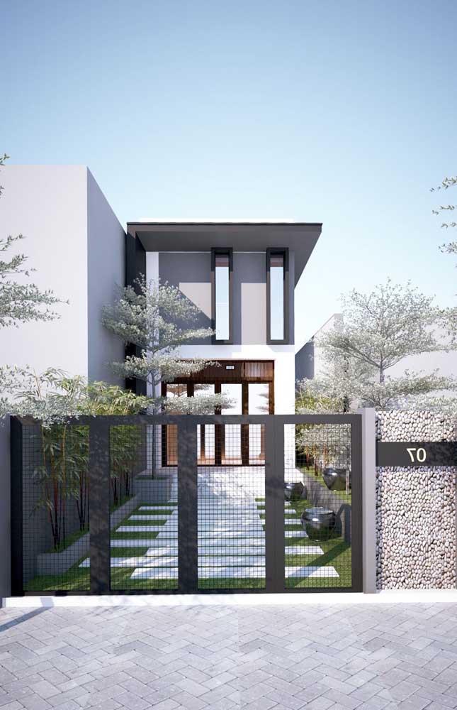 Ideia de casa de alvenaria pequena e moderna com janelas na fachada e portão de ferro para a entrada da garagem