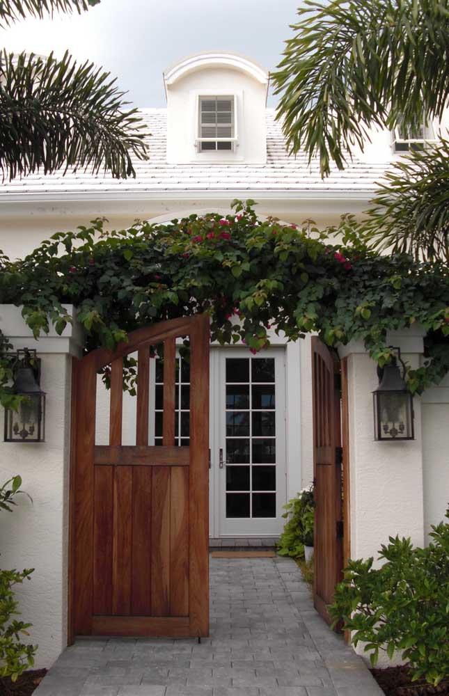 Um modelo encantador de construção de casa de alvenaria com estilo clássico e delicado; destaque para o portão de madeira na entrada