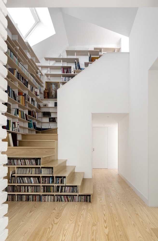 Além de aproveitar os degraus da escada, use a parede para instalar uma estante de livros.