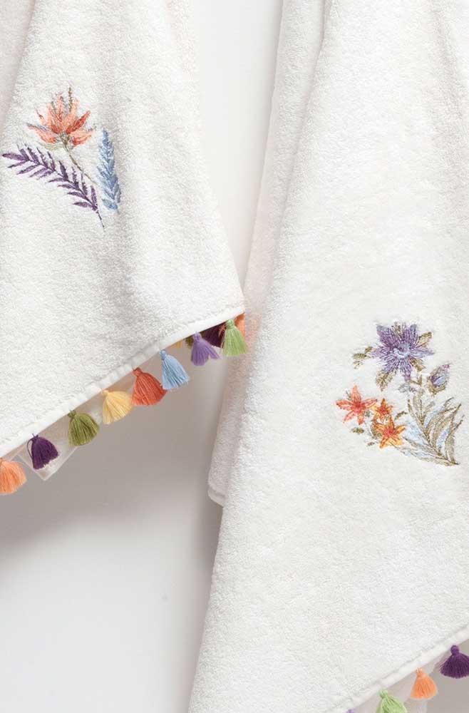 Super delicada, essa toalha branca recebeu um pequeno bordado de flor complementado pelo barrado de franjas coloridas
