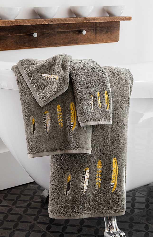 Penas bordadas em amarelo para contrastar com a cor cinza da toalha