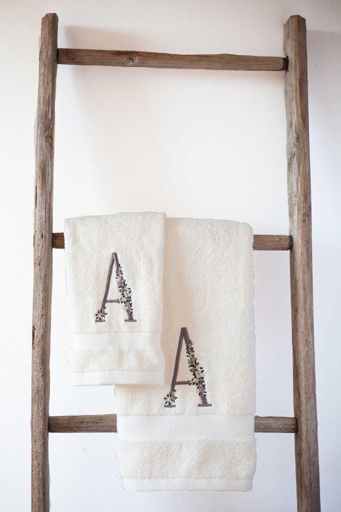 Iniciais do nome bordados no conjunto de toalha de rosto e banho