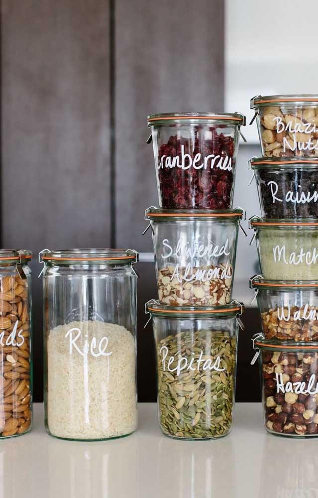 Aqui, os potes de vidro decorados foram personalizados para armazenar os condimentos da cozinha
