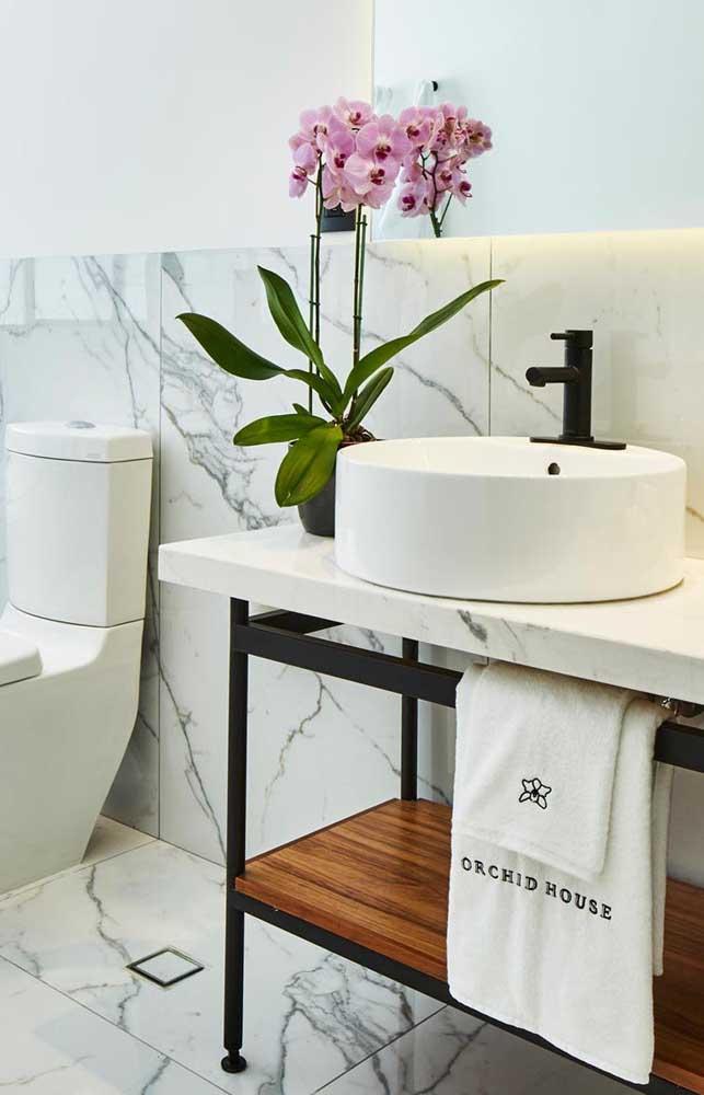 O banheiro branco ajuda a destacar a cor intensa das flores da orquídea Vanda