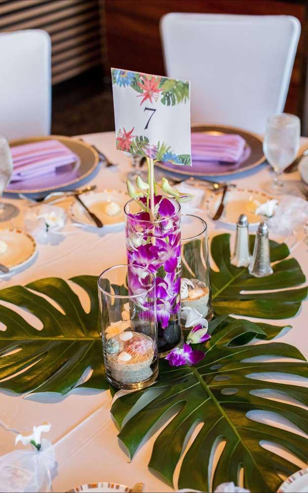 Flores de Vanda e folhas de costela de adão no arranjo da mesa