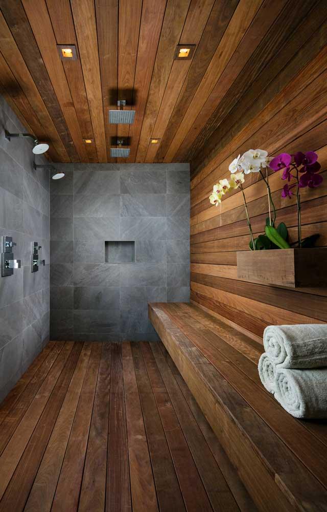 Esse banheiro com revestimento em madeira não poderia ficar melhor do que com o arranjo de orquídeas Vanda