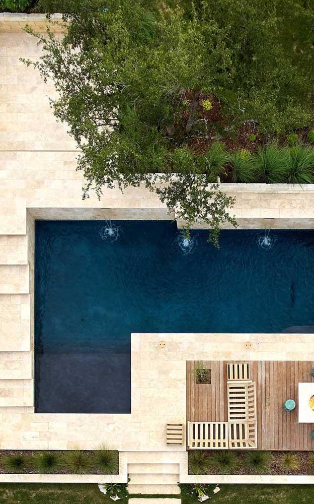 Vista de cima da área da piscina da casa com piso em pedra São Tomé