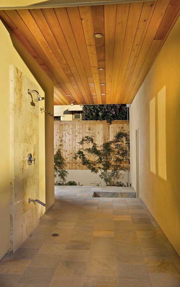 A ducha depois do banho de piscina fica mais agradável com o espaço revestido em pedra São Tomé amarela