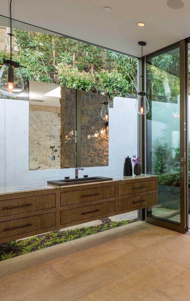 O banheiro elegante e rústico combinou perfeitamente com o piso em pedra São Tomé