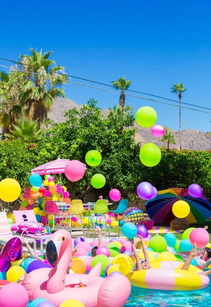 Para fazer a decoração festa na piscina, encha a piscina de bexigas coloridas e aposte em elementos decorativos com cores mais quentes.